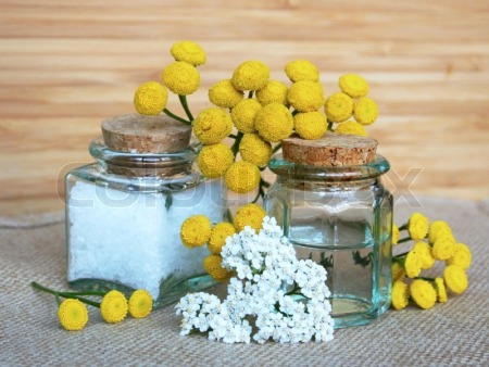3120790-bottles-of-essential-oil-and-sea-salt-with-yellow-camomiles-in-spa-composition